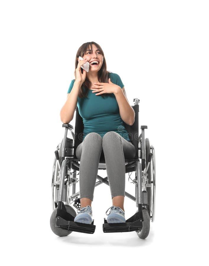 Jonge vrouw in rolstoel die door mobiele telefoon op witte achtergrond spreken stock foto