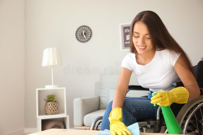 Jonge vrouw in rolstoel schoonmakende lijst thuis stock fotografie