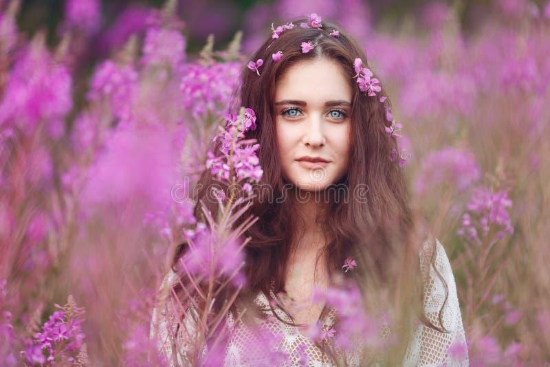 Jonge vrouw in roze bloemen stock foto