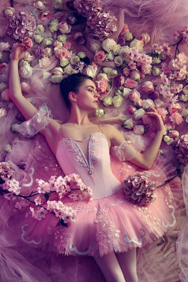Jonge vrouw in roze die ballettutu door bloemen wordt omringd stock afbeeldingen
