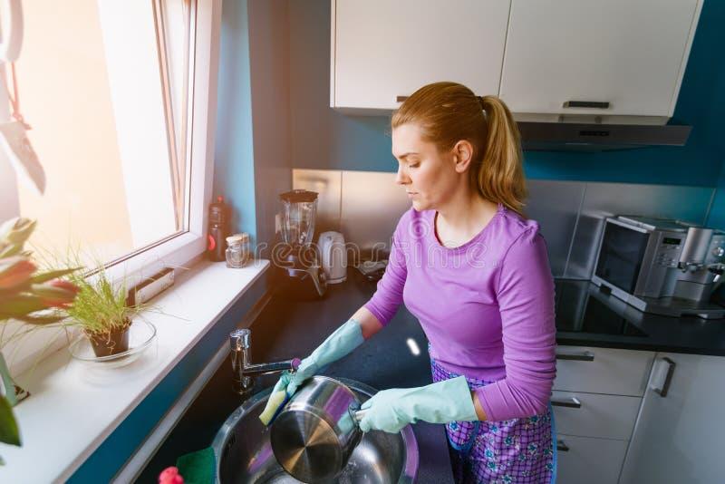 Jonge vrouw in rubberhandschoenen die schotels wassen stock foto
