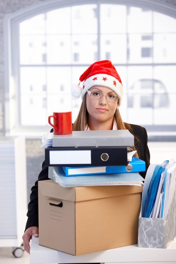 Jonge vrouw in santahoed teneergeslagen in bureau stock foto's