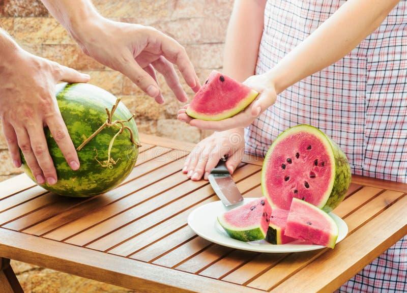 Jonge vrouw in schort die aan man plak van verse watermeloen geven royalty-vrije stock foto