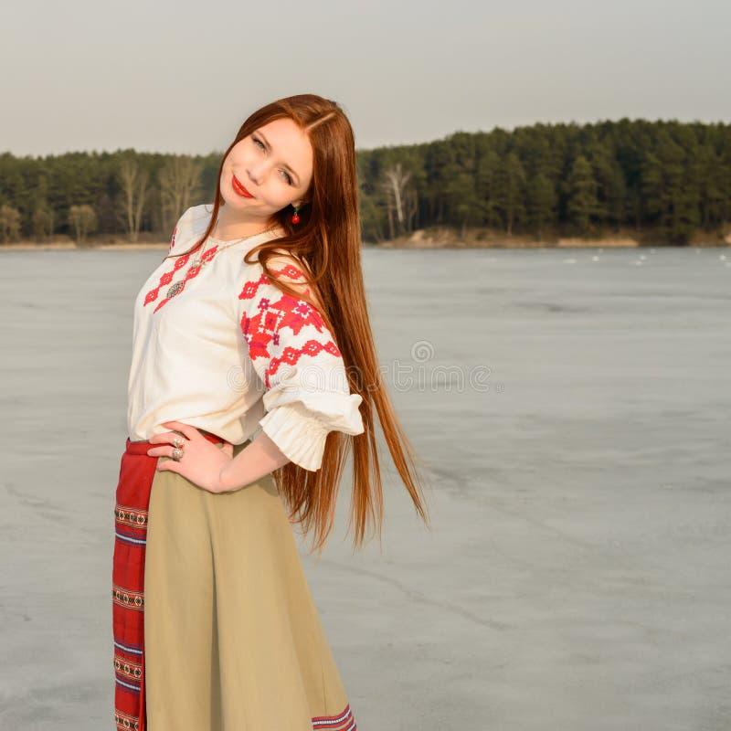 Jonge vrouw in Slavisch Witrussisch nationaal origineel kostuum in openlucht stock fotografie