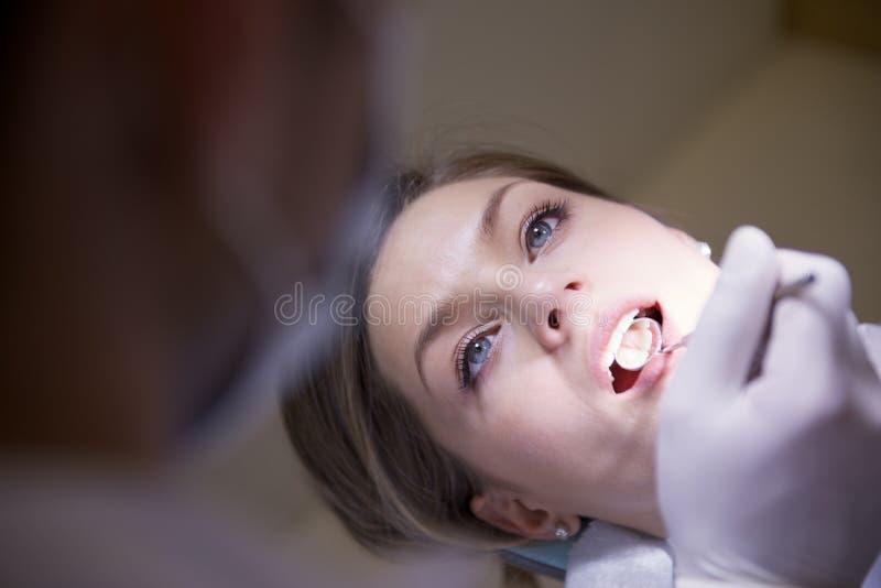 Jonge vrouw in tandkliniek met tandarts die tandenhygiëne controleren stock afbeeldingen