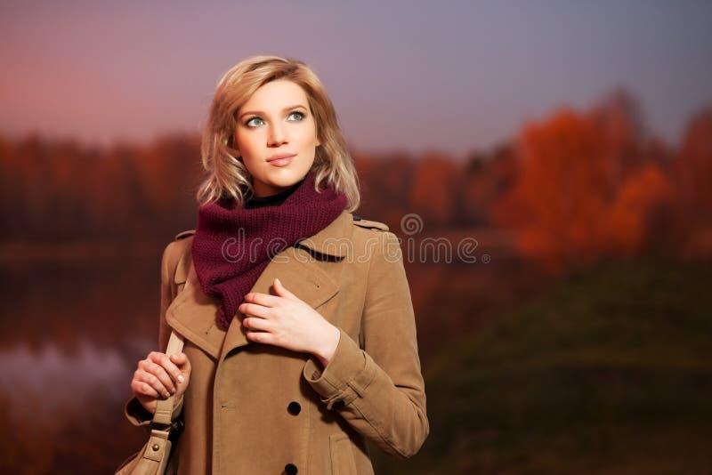 Jonge vrouw tegen een achtergrond van de de herfstaard royalty-vrije stock afbeelding