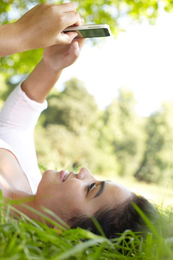 Jonge Vrouw Texting die in de Zomerpark liggen stock fotografie