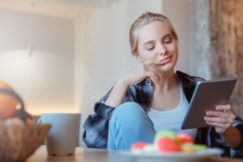 Jonge vrouw thuis in de keuken het drinken thee die digitale tablet gebruiken stock afbeeldingen