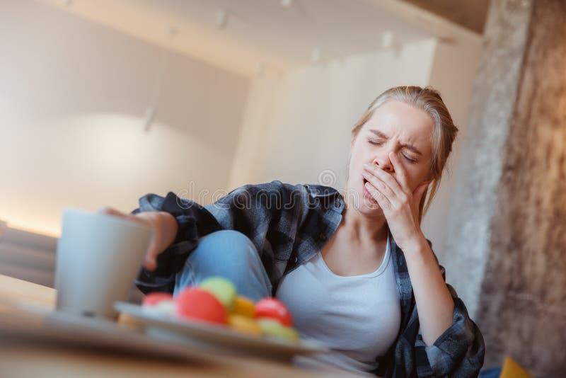 Jonge vrouw thuis in de keuken het drinken thee geeuw royalty-vrije stock fotografie