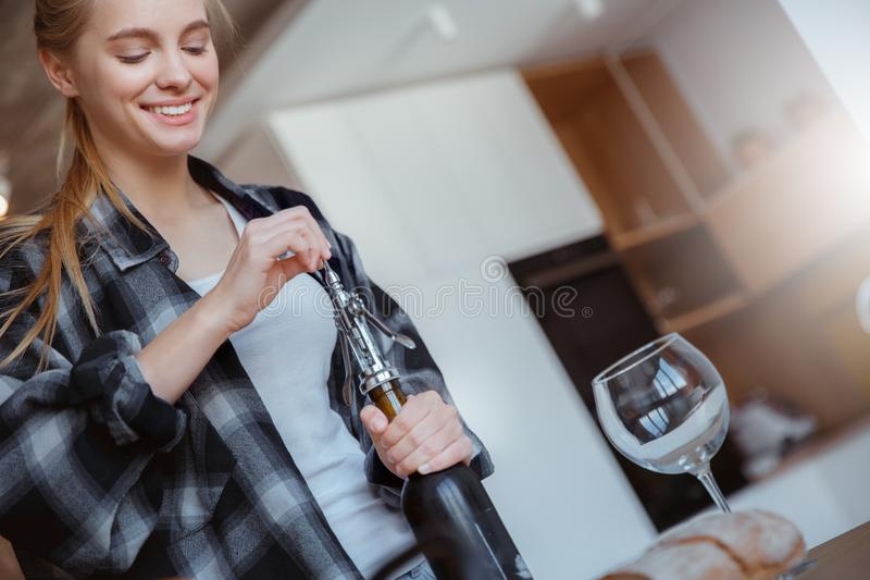Jonge vrouw thuis in de keuken het openen wijn stock foto's