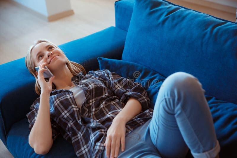 Jonge vrouw thuis in de woonkamer die op bustelefoongesprek liggen royalty-vrije stock fotografie