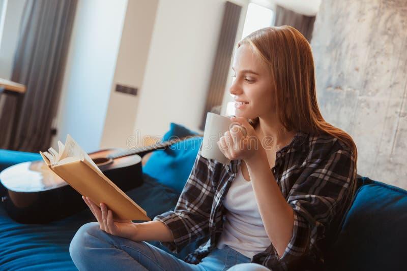 Jonge vrouw thuis in het boek van de woonkamerlezing stock fotografie