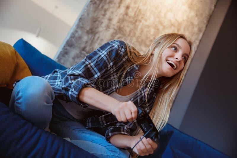 Jonge vrouw thuis in woonkamer opgewekt spelen stock afbeeldingen