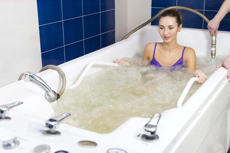 Jonge vrouw tijdens hydromassage royalty-vrije stock afbeelding