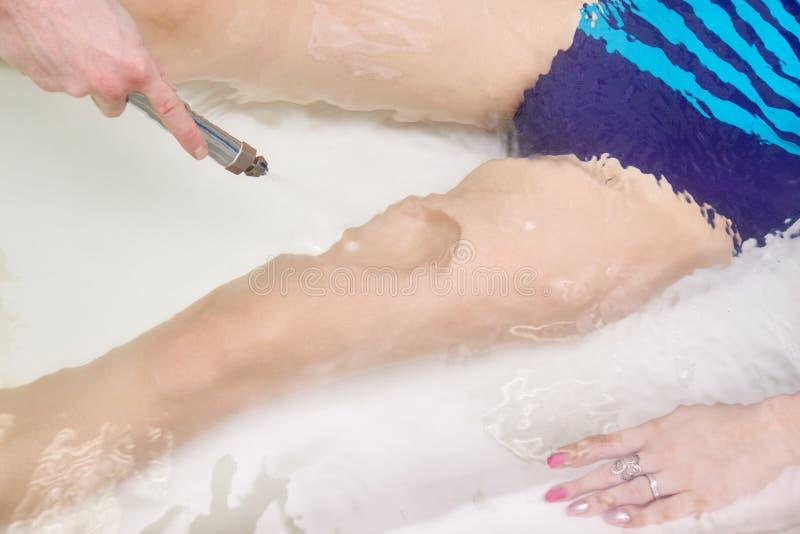 Jonge vrouw tijdens hydromassage in beauty spa salon stock fotografie
