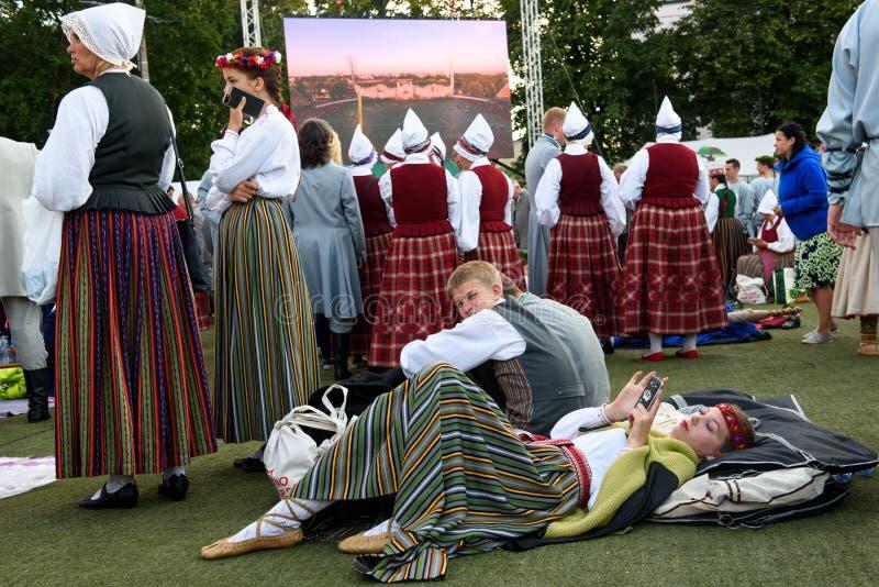 Jonge vrouw in traditionele Letse volkskleding die ter plaatse en met smartphone vóór Dansprestaties liggen ontspannen stock afbeeldingen