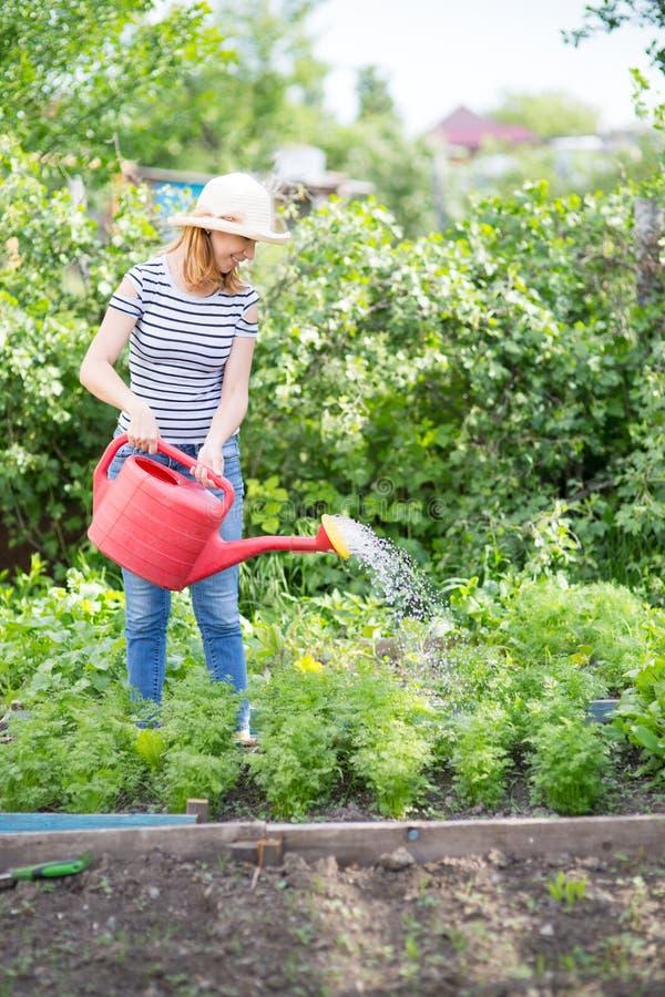 Jonge vrouw in tuin stock foto