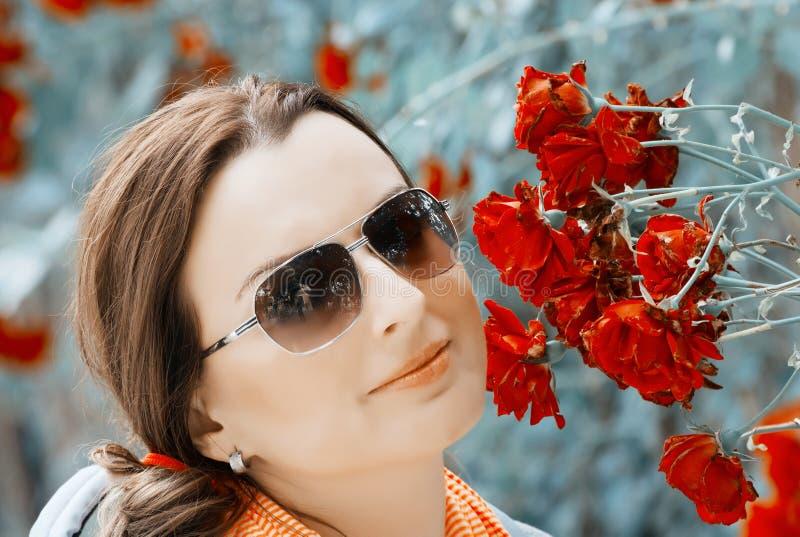 Jonge vrouw in tuin met rode rozen stock foto