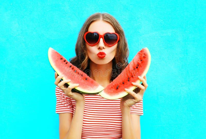Jonge vrouw van het manierportret houdt de vrij plak van watermeloen en blaast lippen royalty-vrije stock fotografie