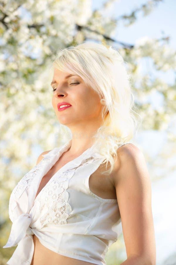 Jonge vrouw voor bloeiende boom royalty-vrije stock afbeeldingen