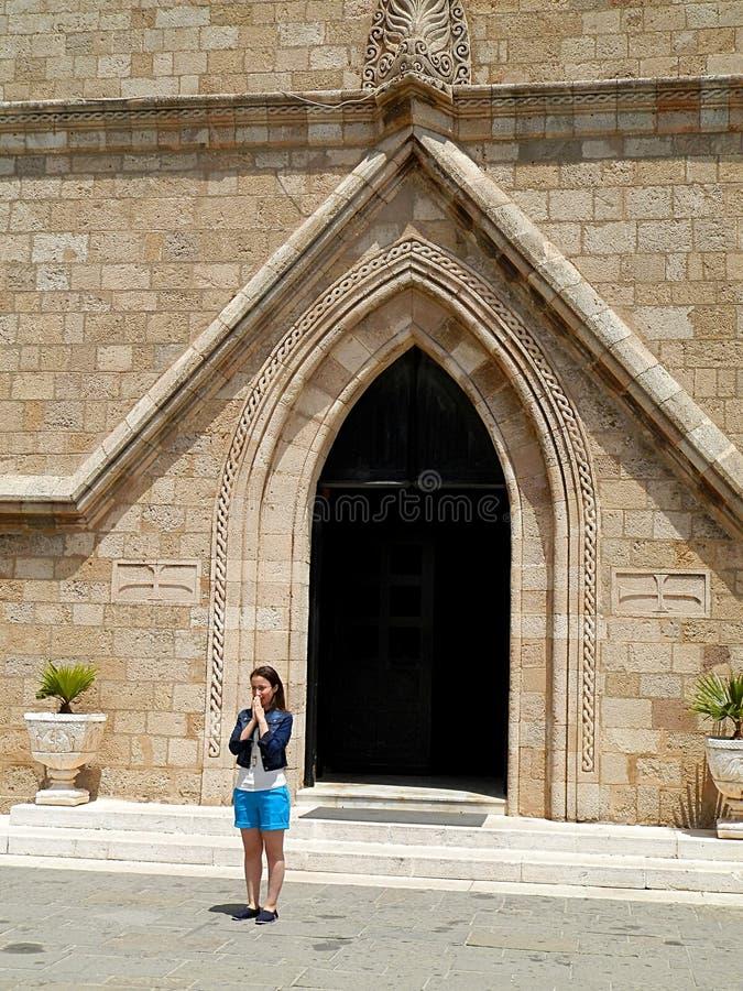 Jonge vrouw voor een kerkpoort royalty-vrije stock fotografie