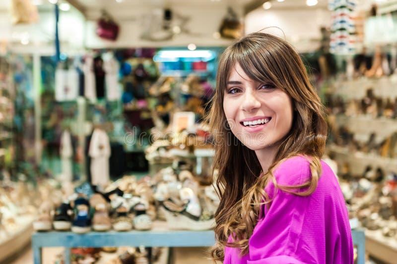 Jonge vrouw vooraan een schoenenwinkel royalty-vrije stock afbeeldingen