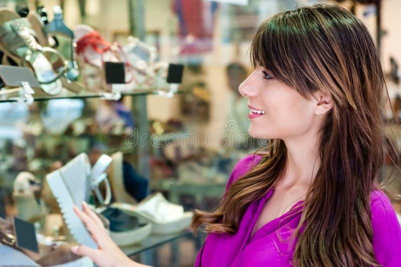 Jonge vrouw vooraan een schoenenwinkel stock fotografie