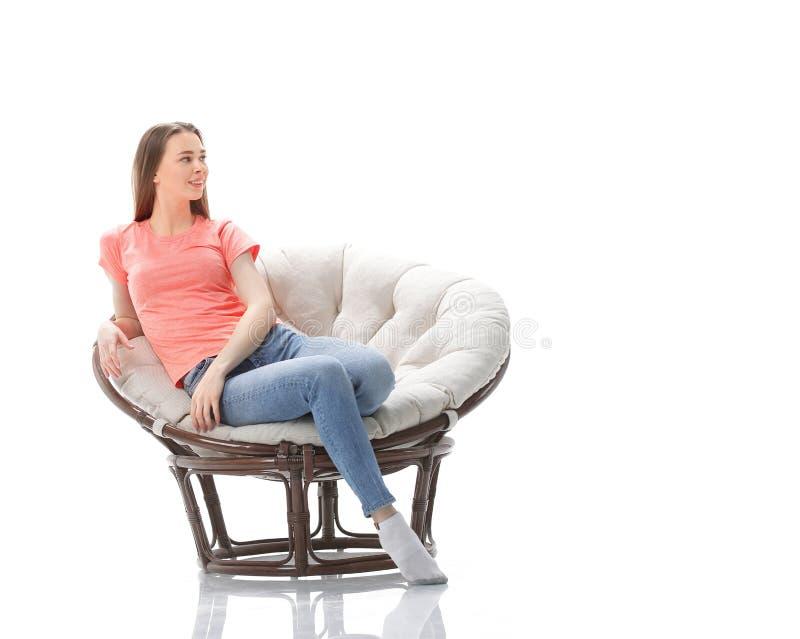 Jonge vrouw in vrijetijdskledingszitting als comfortabele voorzitter Foto met exemplaarruimte stock afbeeldingen