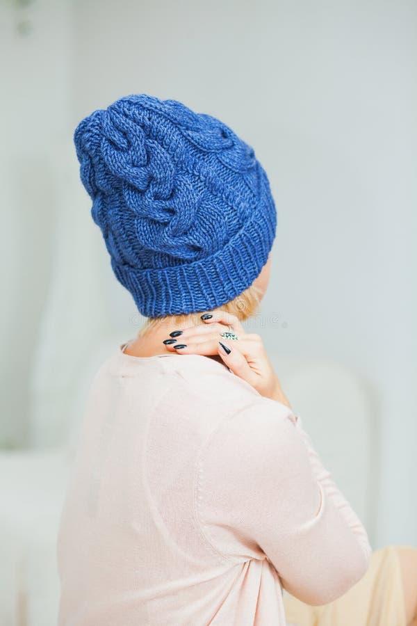 Jonge vrouw in warme donkerblauwe met de hand gebreide hoed thuis stock foto