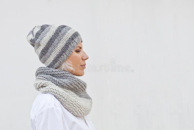 Jonge vrouw in warme grijze gebreide hoed en haarband stock foto