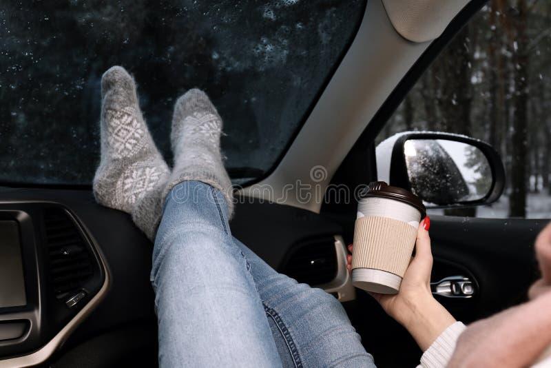Jonge vrouw in warme sokken met koffie die binnen auto rusten stock foto