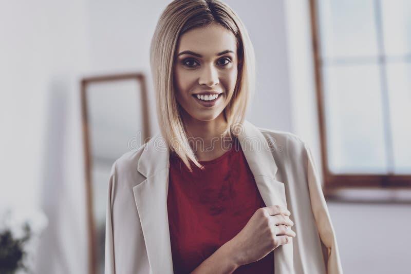 Jonge vrouw wat betreft haar jasje die over schouders worden geworpen royalty-vrije stock foto