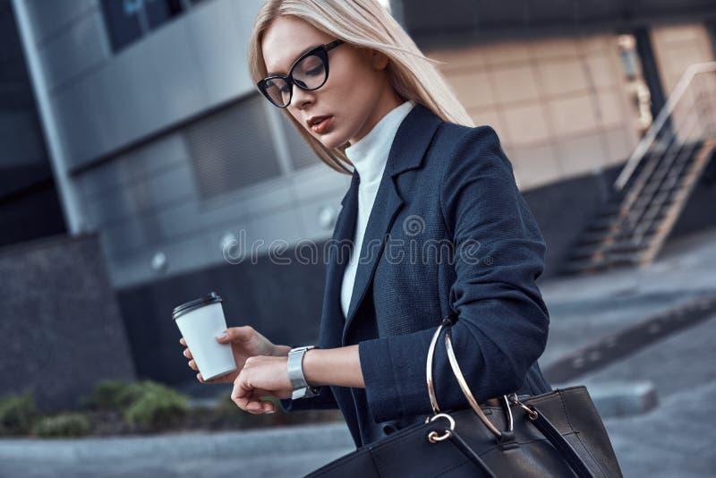 Jonge vrouw wathes bij haar polshorloge In één haar hand coffe, in een andere handtas stock fotografie