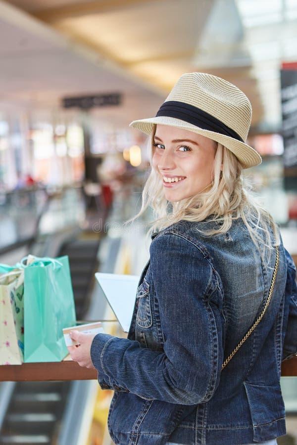 Jonge vrouw in winkelcomplex met creditcard royalty-vrije stock foto
