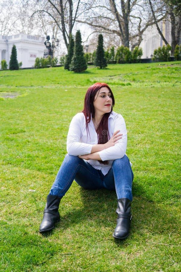 Jonge vrouw in wit overhemd en jeans die op een groen gras zitten royalty-vrije stock fotografie