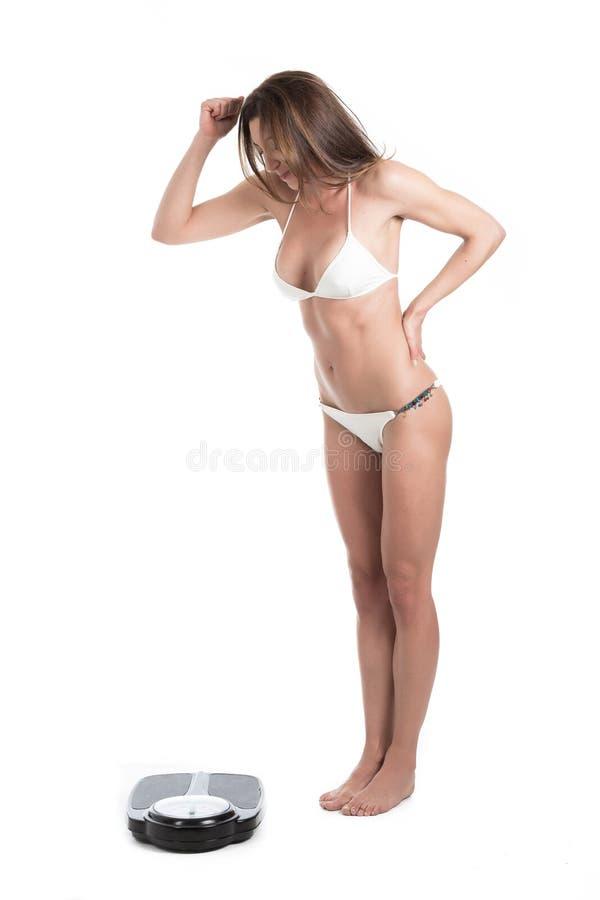 Jonge vrouw in witte bikini droevig en woedend op gewichtsschalen Geschikt en gezond concept Geïsoleerd over witte achtergrond royalty-vrije stock afbeelding