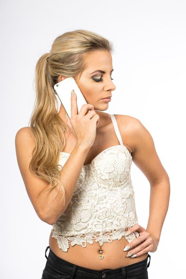 Jonge vrouw in witte blouse Het blondemeisje spreekt op de celtelefoon Wijfje met telefoon Onderneemstervraag met smartphone royalty-vrije stock afbeelding