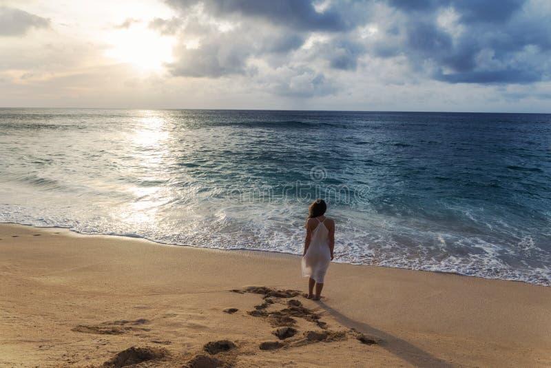 Jonge vrouw in witte kleding die op het strand bij zonsondergang lopen en bij de zon staren stock foto's