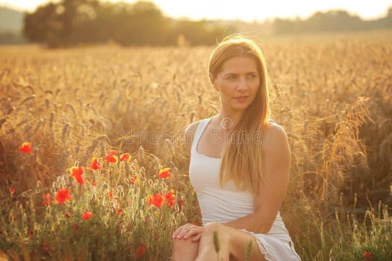 Jonge vrouw in witte kleding, die op tarwegebied zitten, rood papaverne royalty-vrije stock foto