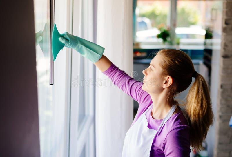 Jonge vrouw in witte schort schoonmakende vensters stock foto's