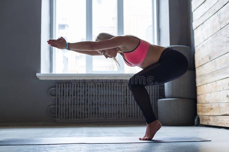 Jonge vrouw in yogaklasse, te stellen vinyasaovergang stock foto's