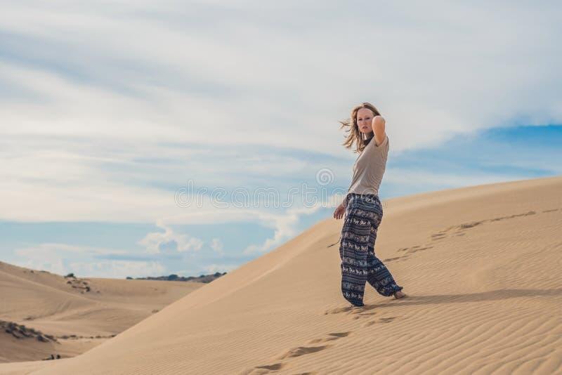 Jonge vrouw in zandige woestijngang alleen tegen zonsondergang bewolkte hemel stock foto's