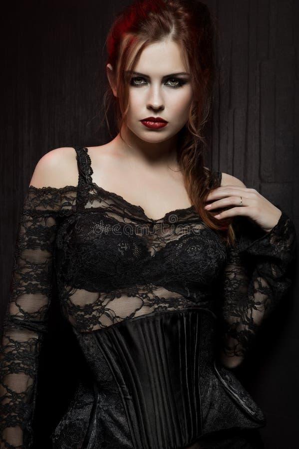 Jonge vrouw in zwart gotisch kostuum royalty-vrije stock afbeeldingen