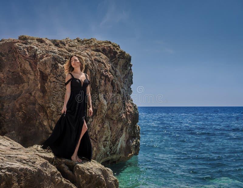 Jonge vrouw in zwarte kleding op de rotsen stock afbeeldingen
