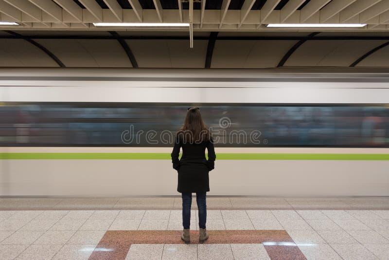 Jonge vrouw in zwarte laag bij het ondergrondse platform royalty-vrije stock foto