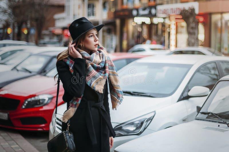 Jonge vrouw in zwarte laag, hoed en sjaal meisje die rond stad lopen royalty-vrije stock fotografie