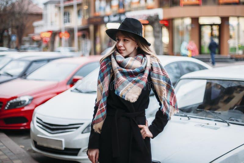 Jonge vrouw in zwarte laag, hoed en sjaal meisje die rond stad lopen royalty-vrije stock foto