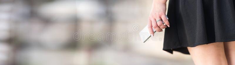 Jonge vrouw in zwarte rok met mobiele telefoon in haar hand royalty-vrije stock foto