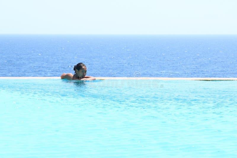 Jonge vrouw in zwembad door overzees stock foto