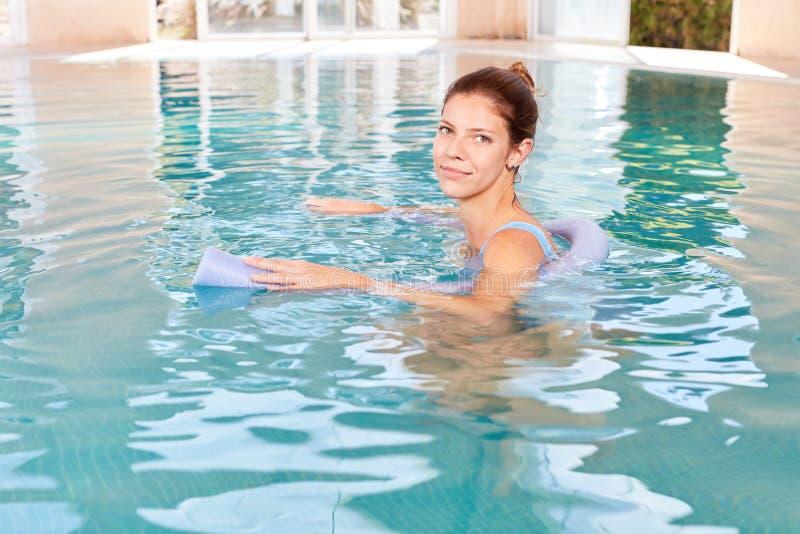 Jonge vrouw in zwembad met het zwemmen hulp stock foto